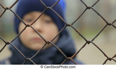 The boy looks at the camera through the grid. The child's...