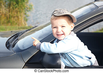 The boy looks out from the automobile