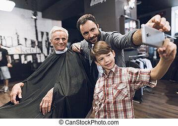 The boy makes selfie on a smartphone with two older men in barbershop.