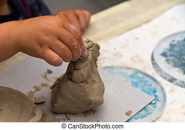 Hands of little boy making toy from clay