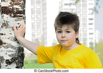 The boy near the birch on the background of the city.