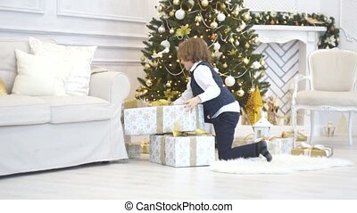 The boy of younger school age collects all gifts under the Christmas tree.