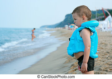 The boy on the beach. In anticipation of the surf