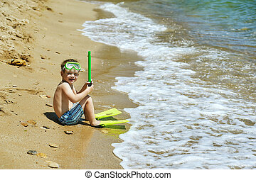 the boy on the beach with a snorkel and fins