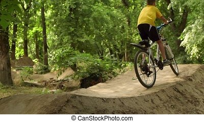 The boy on the bike. Cyclist in the woods. Riding and jumping over obstacles. Bicycle Wheels come off the ground.