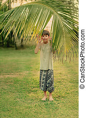 the boy on the green grass holding a palm branch