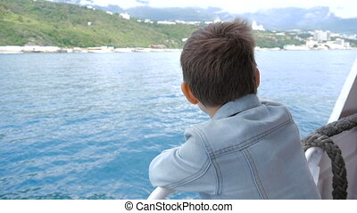 The boy on the ship in windy weather
