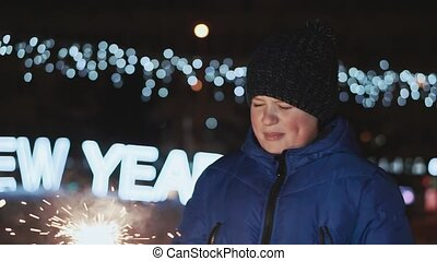 The boy on the street, New Year's Eve. He holds a sparkler and waits for his father to light it.