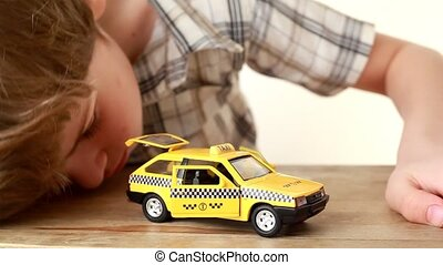 The boy playing with toy taxi car
