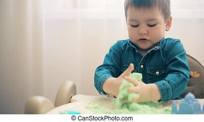 The boy plays with kinetic sand and develops motor skills of hands