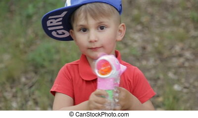 The boy plays with soap bubbles - Cheerful boy with soap...