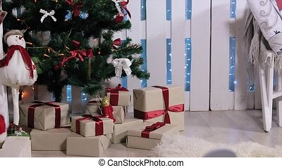 The boy ran to the tree , is a box with a gift, open box, pulls and considers digital tablet, white Room with Fireplace and Christmas Tree, Medium