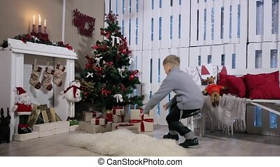 The boy ran to the tree , is a box with a gift, open box, pulls and considers digital tablet, white Room with Fireplace and Christmas Tree