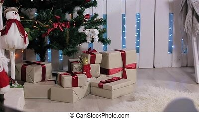 The boy ran to the tree, is a box with a gift, shakes it, pulls and considers smartphone, white Room with Fireplace and Christmas Tree, Medium