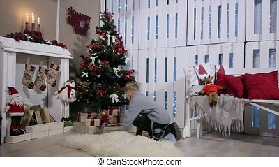 The boy ran to the tree , is a box with a gift, shakes it, pulls and considers smartphone, white Room with Fireplace and Christmas Tree
