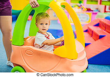 The boy rides a toy colorful car
