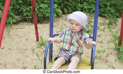 The boy rides on a swing