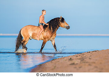 The boy riding a horse in the sea.