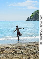 The boy runs in the sea