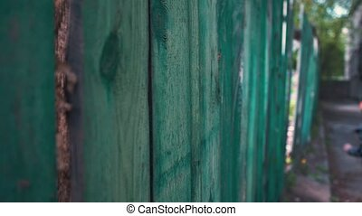 The boy runs through the gap in the old wooden fence,...