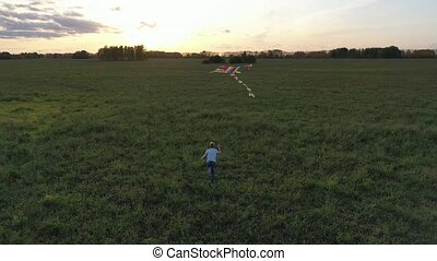 The boy runs with a kite on a green field. Laughter and joy, festive mood. Autumn, Sunset
