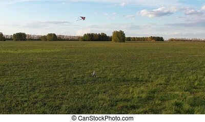 The boy runs with a kite on a green field. Laughter and joy, festive mood. Autumn