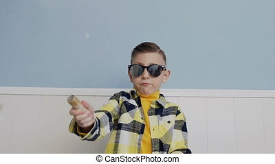 The boy shoots candy and firecracker. young man in black glasses against the background of a white wall
