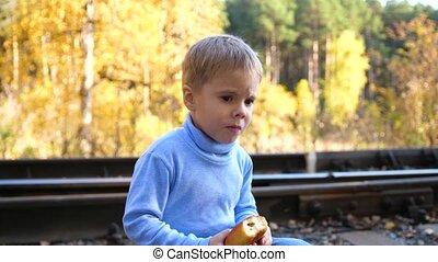 The boy sits and eats a bun on the railway tracks. Autumn...