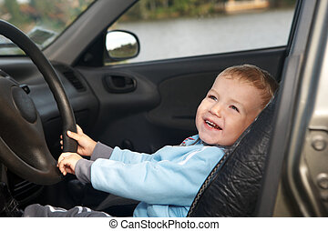 The boy sits in the automobile