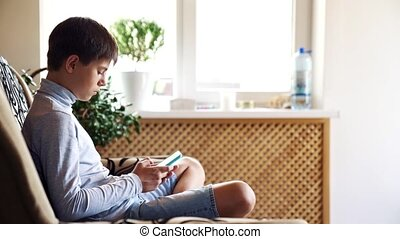 The boy sits on the floor in his room and uses a smartphone. Modern technology in the life of children concept