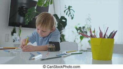 The boy sitting at the table in the living room writes a...