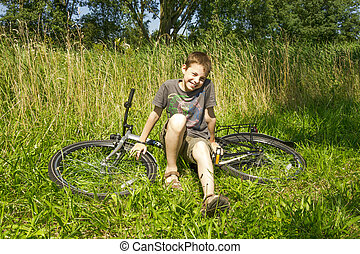 The boy sitting on the bike in grass