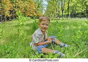 The boy sitting on the grass