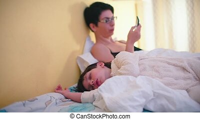The boy sleeps on the bed in white pajamas.
