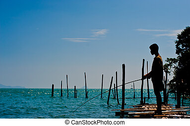 The boy stand on pontoon and  fishing in the sea