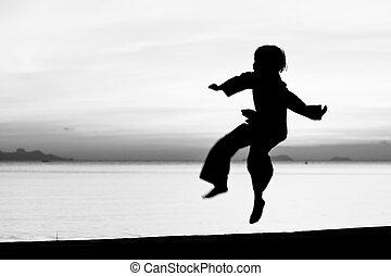 The boy - Silhouette taekwondo boy on the beach at dusk....