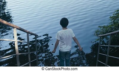 The boy throwing pebbles into the water - The boy going down...