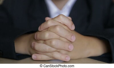 The boy touches his fingers while sitting at his desk