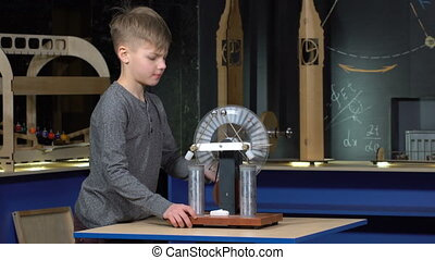 The boy turns the electrostatic machine at a physics lesson