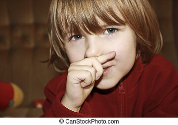 The boy wiping a nose by a finger