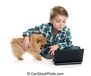 The boy with a laptop and a puppy