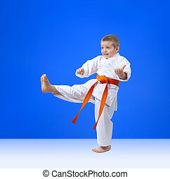 The boy with an orange belt is beating kick leg