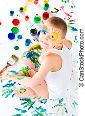 The boy with paints. - The little boy soiled by paints.