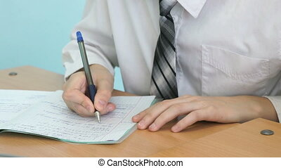 The boy writing the text in the copybook indoors