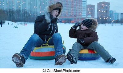 The boys sit on the sled and pushing in the winter