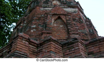 An extreme closeup shot with a tilting view of a red brick Prang's base to the partially rundown vaulted niches of its spire-like tower.
