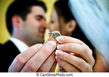 wedding ring - The bride and groom are holding up the ...
