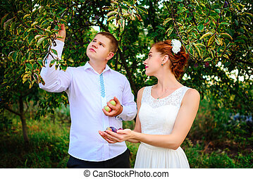 The bride and groom are kissing in the apple orchard, standing under the branches of an apple-tree