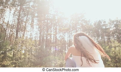 The bride and groom are posing in the forest. The young groom joyfully lifts the bride and circles her in the rays of sunlight. Beautiful background. Happy moment of a loving couple. Summer. Wedding day.
