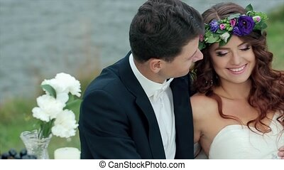 The Bride and Groom are Sitting on a Green Field